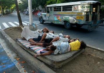 Street children sleep on a discarded mattress on a center island near a road crossing in Manila, Philippines, in April. After 15 years of the Millennium Development Goals, Asia as a region has had the fastest progress, reports the U.N., yet hundreds of m