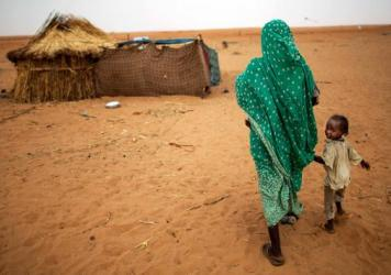 A woman and her daughter walk at the Zam Zam camp for internally displaced people in North Darfur, Sudan, in June 2014. The U.S. and other countries have said that Sudan is committing genocide in Darfur, and the United Nations has an ongoing peacekeeping program. But many in the region still live in fear and misery.