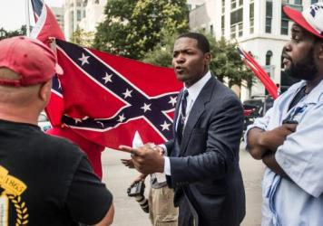 Jalaludin Abdul-Hamid, a protester against the Confederate flag that flies outside the South Carolina Statehouse, speaks to a flag supporter Tuesday. The state's House is taking up the issue of moving the flag Wednesday.