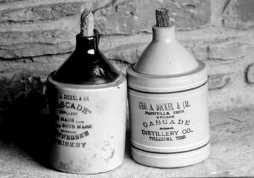 Before distilleries used glass bottles, many of them offered liquor stores branded ceramic jugs that could be filled and sold to customers. This pair of George Dickel jugs was used around 1900. From<em> The Art of American Whiskey</em> by Noah Rothbaum.