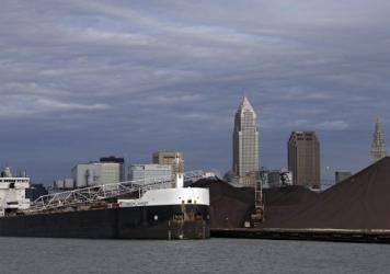 The freighter American Mariner discharges its load of iron ore in Cleveland last November. Prices for iron ore and other commodities have plunged amid economic uncertainty in China and Europe.