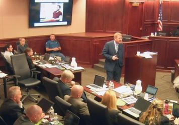 In this image taken from video, James Holmes (upper far left) listens to defense attorney Daniel King give closing arguments during Holmes' trial in Centennial, Colo., on Tuesday. Holmes was found guilty Thursday of first-degree murder in the deaths of 1