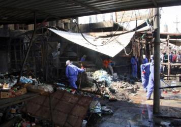 Iraqi workers clean the site of a truck bomb attack that hit the area a day earlier at Khan bani Saad town, eastern Baghdad, Iraq, on Saturday. At least 115 people were killed in what's described as the single deadliest such attack in the country in a de