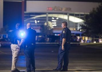 Officials stand by the scene outside a movie theater where a man opened fire on filmgoers Thursday in Lafayette, La. At least two were fatally wounded and seven others injured before the gunman killed himself.