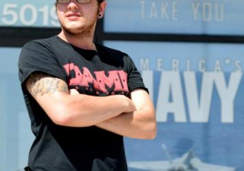 """Zachary Gallegos, 23, stands guard outside the Armed Services Recruiting Center on Thursday in Sioux Falls, South Dakota. The Pentagon has asked such self-appointed """"armed citizens"""" to leave, citing security concerns."""