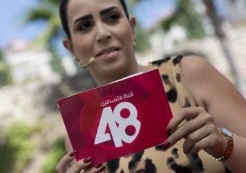 Afaf Shini, a host on the Palestine 48 TV channel, holds a reading card with the satellite channel's logo during a morning broadcast in Ramallah in July. Israel shut down operations just days after the launch.