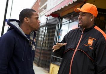 "Ricardo ""Cobe"" Williams, wearing the cap, served time for attempted murder before joining CeaseFire as a ""violence interrupter."" Above, he talks with Lil Mikey in a scene from the documentary <em>The Interrupters.</em> Lil Mikey, who'd also been in prison, went on to become an outreach worker with the organization."