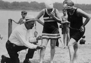 """A """"beach cop"""" measures bathing suits in Washington, D.C., in 1922."""