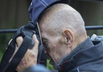 Irwin Lipkin, one of Bernard Madoff's longest-serving employees, covers his face as he is pushed in a wheelchair leaving U.S. court in New York on Wednesday.