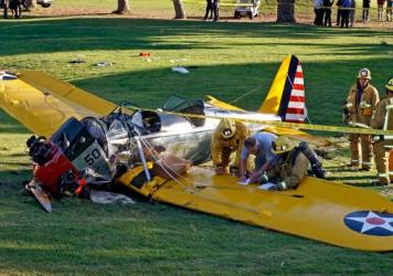 Officials work on the scene of a vintage airplane that had been piloted by actor Harrison Ford when it crash-landed in March on the Penmar Golf Course in the Venice area of Los Angeles. Federal safety investigators have concluded that a problem with a carburetor part led to engine failure.