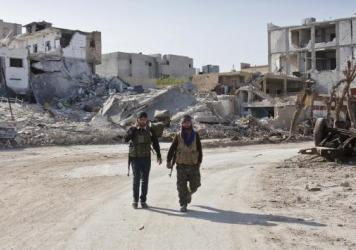 Kurdish rebels in northern Syria walk near the devastated town of Kobani last November. The U.S. bombing campaign helped the Kurds push back the Islamic State from the area. But overall, the U.S. operation against ISIS in Iraq and Syria has shown only limited gains in the past year.