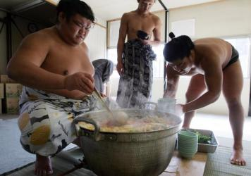 Sumo wrestlers serve up <em>chanko-nabe</em> at Musashigawa Sumo Stable in 2007 in Osaka, Japan.