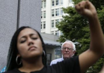 Mara Jacqueline Willaford, left, holds her fist overhead as Democratic presidential candidate Sen. Bernie Sanders, I-Vt., stands nearby at a rally Saturday. The activists took over the microphone and refused to allow Sanders to speak.