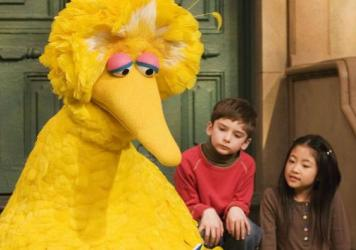 Big Bird, played by puppeteer Caroll Spinney, reads to Connor Scott and Tiffany Jiao during a taping of <em>Sesame Street</em> in 2008 in New York