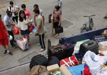People carry their luggage as they are evacuated Saturday in the aftermath of a huge explosion that rocked the port city of Tianjin, China. Explosions and a fireball at a chemical warehouse killed at least 85 people in the north-eastern Chinese port city