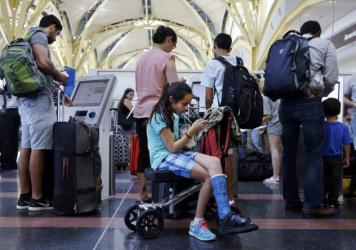 Alisha Lalani, 10, of Ft. Lauderdale, Fla., looks at her phone as her mother and brother check in for their flight to Miami at Washington's Reagan National Airport. Their flight was one of thousands delayed as a result of a technical glitch with an FAA a