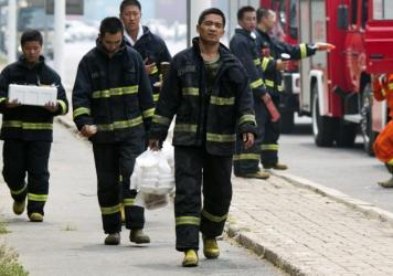 Chinese firefighters collect lunch as they wait near the site of an explosion in northeastern China's Tianjin municipality on Saturday. Officials say that 85 firefighters are among the nearly 100 people still missing from the blasts.