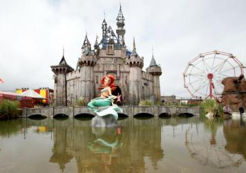 A glitched Little Mermaid piece sits in front of a dismal castle as part of the artist Banksy's biggest show to date, titled <em>Dismaland,</em> at Tropicana in Weston-super-Mare, England.