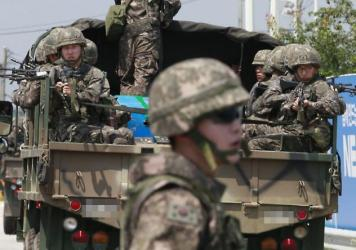 Armed South Korean soldiers cross a bridge on a truck in the border town of Paju, South Korea, on Sunday, as negotiators from the South and North Korea resumed talks.