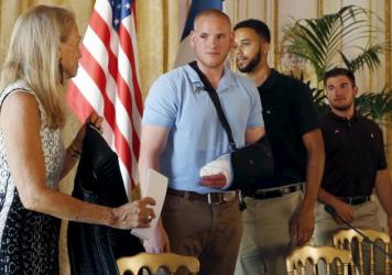 U.S. ambassador to France Jane Hartley presents U.S Airman First Class Spencer Stone, student Anthony Sadler and National Guardsman Alek Skarlatos (left to right) as they attend a news conference at the U.S. Embassy in Paris, France, on Sunday.