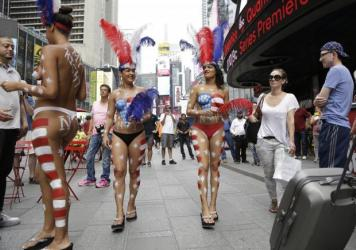 Topless women wearing American flag body paint walk around Times Square in New York City on Sunday.