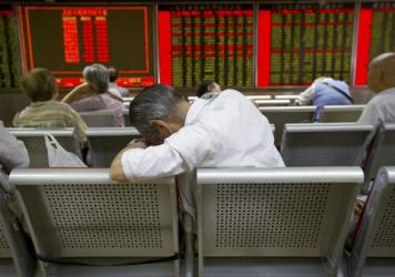 Chinese investors monitor stock prices at a brokerage house in Beijing on Tuesday.