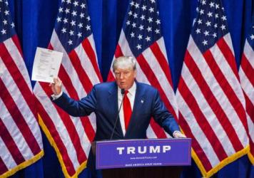 "Donald Trump holds financial documents at his campaign announcement in June. He had said he didn't need donors because he could pay for his campaign himself, but he recently said he'd be open to people ""investing"" in his campaign."