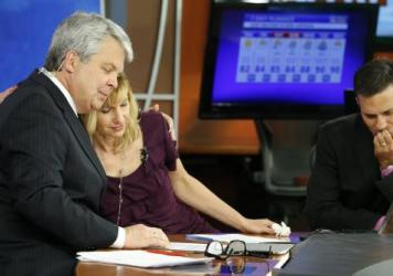 WDBJ-TV news morning anchor Kimberly McBroom gets a hug from visiting anchor Steve Grant as meteorologist Leo Hirsbrunner reflects Thursday after their early morning newscast at the station.