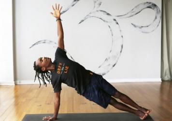Walter Mugbe, a teacher with the Africa Yoga Project, demonstrates side plank in the Bethesda, Maryland, studio of Down Dog Yoga.