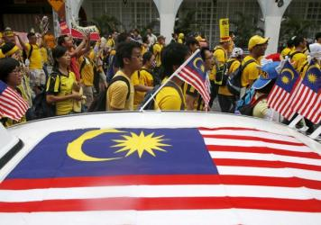 """Supporters of pro-democracy group """"Bersih"""" (Clean) pass a taxi decorated with Malaysian flags as they march towards Dataran Merdeka in Malaysia's capital city of Kuala Lumpur, on Saturday. The group is protesting alleged corruption at the top levels of government."""