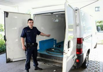 Inspektor Jan Gieber of Austrian police shows the inside of the large van outside the police station in Braunau, Upper Austria, on Sunday, where the children were found among 26 migrants trying to reach Europe.