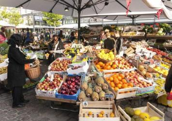 Copenhagen, Denmark - October 11, 2014: fruits and vegetables stalls at market in Copenhagen. Customers are choosing goods for themselves. These stalls is located between market halls where one can find over 60 stands with everything from fresh fish and meat, as well as small places to get a quick bite. It is located near Nørreport metro station.