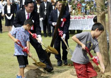 Noraha Mayor Yukiei Matsumoto, rear left, plants a tree with children of Naraha residents during an event in Naraha, Fukushima, northern Japan, on Saturday.