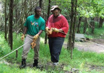 Kalen Gilliam (left) and Justis Jackson take measurements at the Urban Archaeology Corps excavation site about 10 miles outside of Richmond, Va.