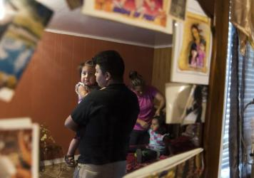 Jose Arriaga holds his youngest sister, Kaylin, while his mother, Veronica Arriaga, gets his middle sister, Krystal, ready for school. Jose just began his freshman year at Booker T. Washington High School in Tulsa, Okla.
