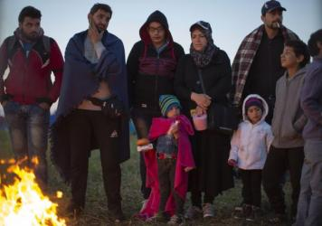 Migrants who crossed the border from Serbia into Hungary Monday night use a fire to keep warm at dawn at a collection point Tuesday. So far in 2015, more than 367,000 refugees and migrants have crossed the Mediterranean to seek safety and better prospect