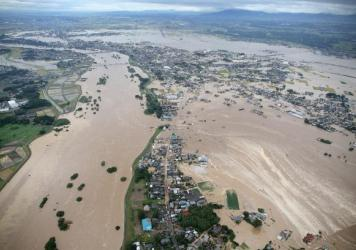 Floodwaters from the burst Kinugawa River (left) flow into a residential area (right) in Joso, Ibaraki Prefecture, on Thursday. The city is northeast of Tokyo.