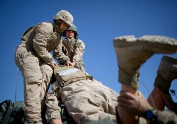 """Marine Lance Cpls. Julia Carroll (left) and Paula Pineda lift """"Carl"""" — a 220-pound test dummy — during training in March in California. Female Marines have completed months of training and are now waiting to hear whether they will be allowed to serve"""