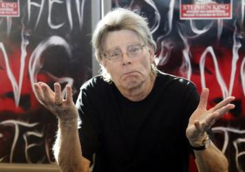 Stephen King poses for the cameras during his promotional tour for the novel <em>Doctor Sleep </em>in 2013. Now, just imagine him in a suit and tie, with a medal around his neck.