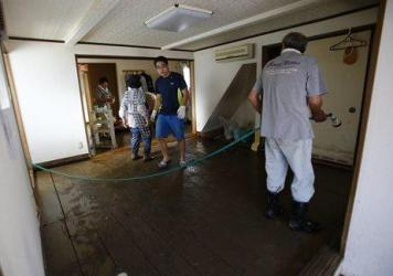 Family members clean a house on Friday after the flooding in Shimotsuma, near Joso, Ibaraki prefecture, northeast of Tokyo.