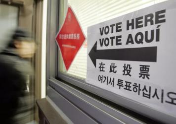 A voter enters a polling place with multilingual instructions in New York City's Chinatown in 2006. Analysts have described the Asian-American political evolution as one of the most dramatic swings in recent presidential voting behavior across any demographic.