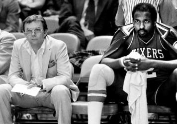 Moses Malone (right) rests on the bench during a game against the New York Knicks in 1984. Malone, a three-time NBA MVP, has died at the age of 60.