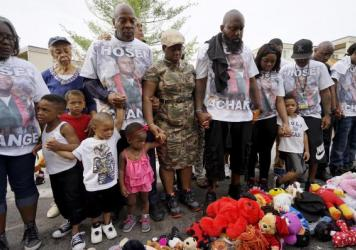 A new report by a governor-appointed commission suggests ways for communities in St. Louis to move forward after the police killing of Michael Brown last summer. Here, Brown's father and other relatives pray at a memorial to Brown last month.