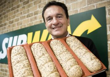 Subway co-founder Fred DeLuca poses carrying bread for sandwiches.