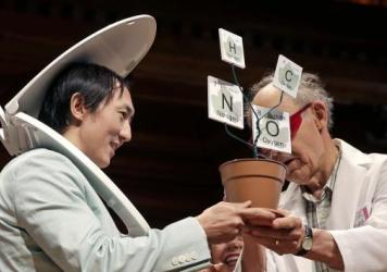 While wearing a toilet seat on his head, David Hu accepts the Physics Prize, for his research on the principle that mammals empty their bladders of urine in about 21 seconds, from Dudley Herschbach, right, the 1986 Nobel Laureate in Chemistry, while bein