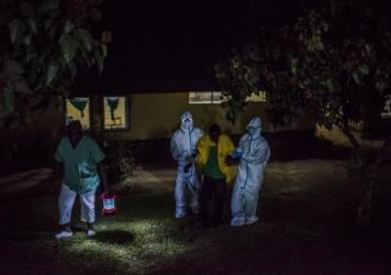 Health workers at an Ebola treatment center, run by Doctors Without Borders, greet man whose family brought him in by wheelbarrow. They suspected that he had the virus. The center is in Foya, Liberia.