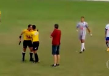A referee is restrained at an amateur game in Brazil after running onto the field brandishing a pistol.