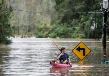 A man kayaks on Tall Pines Circle in Columbia, S.C., Sunday. Many parts of South Carolina experienced record rainfall over the weekend, triggering widespread flooding.