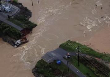 People survey the Carys Lake dam and bridge in Columbia, S.C., Tuesday. The dam was washed away after surging waters swept through the area. Farther downstream, Forest Lake overspilled its dam and flooded other parts of the Columbia suburbs.