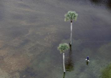 A man makes his way through floodwaters in a parking lot on Isle of Palms, S.C., on Monday.